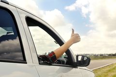 Woman giving a thumb up from car royalty free stock image