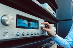 Hand of woman turning up volume of Hi-Fi amplifier. In her home stock photography