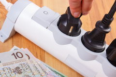 Hand of woman turns off electrical plug, polish currency money, energy costs Stock Photos