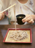 Hand of woman use chopsticks to clamp a noodle on a bamboo dish, japanese noodle, it's call Soba, selective focus at noodle Royalty Free Stock Photos
