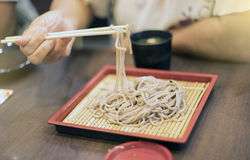 Hand of woman use chopsticks to clamp a noodle on a bamboo dish, japanese noodle, it's call Soba, selective focus at noodle Stock Image
