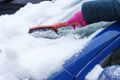 Hand of woman using brush and remove snow from car and windscreen Stock Photos