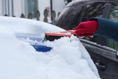 Hand of woman using brush and remove snow from car and windscreen Royalty Free Stock Images