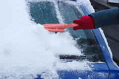Hand of woman using brush and remove snow from car and windscreen Stock Image