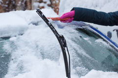 Hand of woman using brush and remove snow from car and windscreen Stock Images