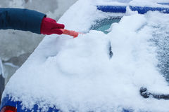 Hand of woman using brush and remove snow from car and windscreen Royalty Free Stock Image