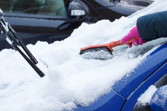 Hand of woman using brush and remove snow from car and windscreen Stock Photography