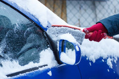 Hand of woman using brush and remove snow from car, windscreen and mirror Royalty Free Stock Photos