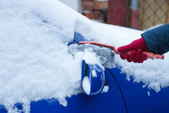 Hand of woman using brush and remove snow from car, windscreen and mirror Stock Photos