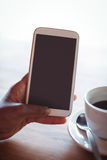 Hand of woman using mobile phone while having coffee Stock Images