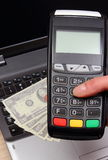 Hand of woman using payment terminal, currencies dollar on laptop in background Royalty Free Stock Photos