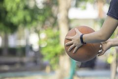 Hand of a woman wearing a watch And holding old basketball stock photo
