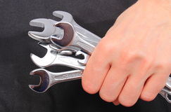 Hand of woman with wrenches on black background Stock Image