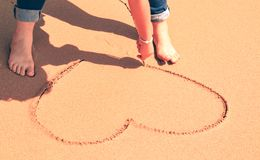 Hand of woman write a heart on the beach. royalty free stock photos