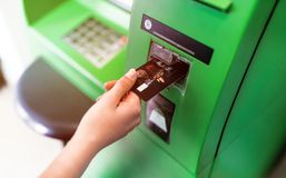 Hand of a women with a credit card, using an ATM. Woman using an atm machine with his credit card. royalty free stock photography