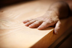 Hand on wood. Closeup of a hand touching a piece of wood Royalty Free Stock Images