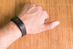 Hand on wood table wearing a fitness tracking Stock Images
