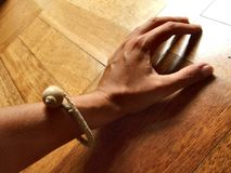Hand on a wooden floor. Female hand with string bracelet on a wooden floor Royalty Free Stock Photography