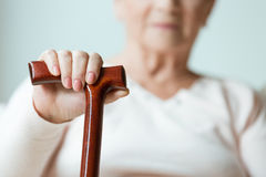 Hand on wooden stick. Sad older lady`s hand placed on wooden walking stick stock photo