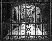 Hand-worked wrought iron gate with internal courtyard of an old. Italian building stock photo