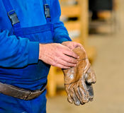 Hand of a worker in a factory. The hand of a worker taking his gloves Stock Photography