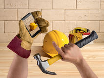 Hand worker with hammer and smartphone, construction tools on br Royalty Free Stock Photos