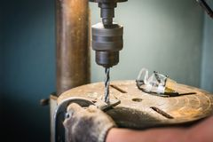 Hand of worker man drills a hole in iron bracket with Pillar dri. Lling machine Royalty Free Stock Photography