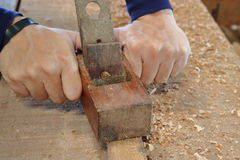 Hand of worker planing a plank of wood using a hand planer royalty free stock photo