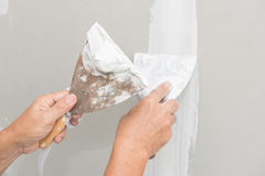 Hand of worker with plaster and trowel to gypsum board Royalty Free Stock Photos