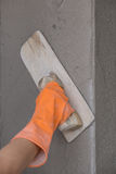 Hand of worker use trowel plastering concrete at wall Royalty Free Stock Images