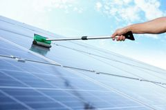 Hand of worker washing solar panels after installation Royalty Free Stock Photo