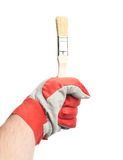 Hand in a working glove holding brush Stock Photos