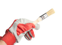 Hand in a working glove holding brush Stock Image