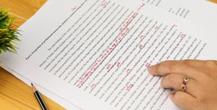 Proofreading paper on table. Hand working on paper for proofreading Royalty Free Stock Photo