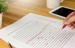 Proofreading paper on table. Hand working on paper for proofreading Stock Photos