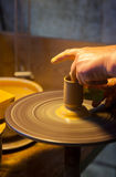 Hand of a working potter making a ceramic vessel on his wheel Stock Image