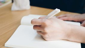 Hand of woman holding a pen for write to a book. Hand of working or student woman holding a pen for write a message to a book or notebook on a wood table Royalty Free Stock Photos