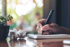 A hand working and writing down on a white blank notebook with screwed up papers on table. Closeup image of a hand working and writing down on a white blank Royalty Free Stock Photos
