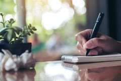 A hand working and writing down on a white blank notebook with screwed up papers on table. Closeup image of a hand working and writing down on a white blank Royalty Free Stock Photography