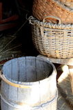 Hand woven baskets and barrels in barn doorway. Homey feel of hand woven baskets and old wood barrel in barn doorway, with sunlight streaming across the face of Stock Photos