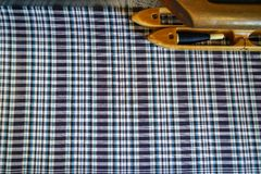 Hand woven cotton fabric in shades of dyed blue and white plaid pattern background with wooden thread shuttle on traditional loom. Thailand Royalty Free Stock Photos
