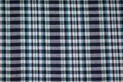 Hand woven traditional cotton fabric in shades of dyed blue and white plaid pattern background. Thailand Stock Photography