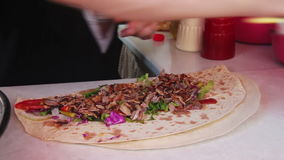 Hand Wrapping Traditional Shawarma with Beef and Vegetables. Hand wrapping traditional shawarma wrap with beef and vegetables. Full HD 1920 x 1080, 29,97fps stock footage
