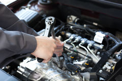 Hand with wrench. Auto mechanic in car repair Royalty Free Stock Photo