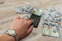 Hand with wrist watch, calculator and dollars on a wooden background. Hand with a wrist watch close up, calculator and hundred dollar bills royalty free stock photos