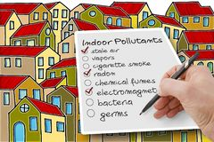 Hand write a check list of indoor air pollutants against a build. Ings background - concetp image with copy space royalty free stock photography