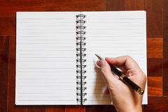 Hand write on notebook with pen. Royalty Free Stock Image