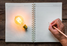 Hand write over Note book. And light bulb Royalty Free Stock Images