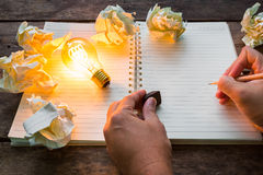 Hand write over Note book and light bulb Royalty Free Stock Photo