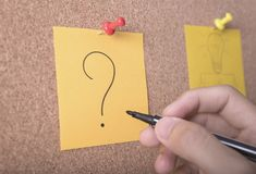 Hand writeing question mark on sticky note or post is on cork Royalty Free Stock Image